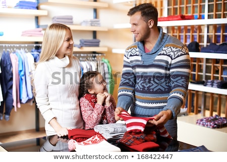 Parents choosing new pullover for their daughter in casualwear department Stock photo © pressmaster