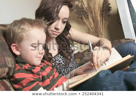 A Babysitter Writing something on a book Stock photo © Lopolo