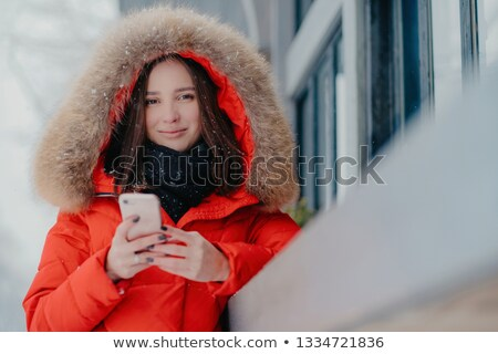 Outdoor shot of lovely dark haired Caucasian woman in winter street clothes, holds modern cell phone Stock photo © vkstudio