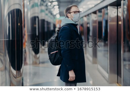 Preventive measures in public places. Sideways shot of man in medical mask stands on metro station,  Stock photo © vkstudio