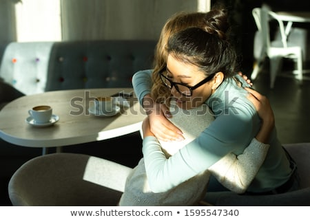 depressed young women hugging on a sofa in a living room stock photo © wavebreak_media