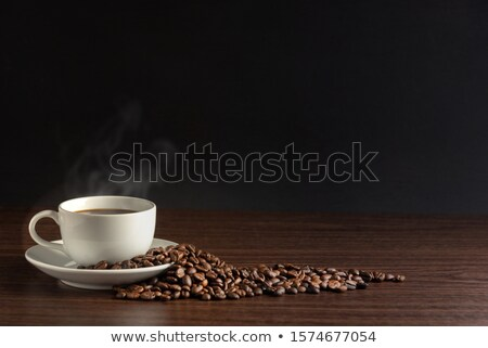 coffee cup on dark roasted beans stock photo © elisanth