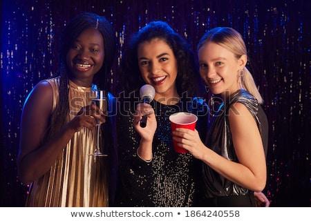 Stok fotoğraf: Three Smiling Women Dancing And Singing Karaoke