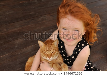 child with red hair is looking happy and friendly sitting in a o Stock photo © meinzahn
