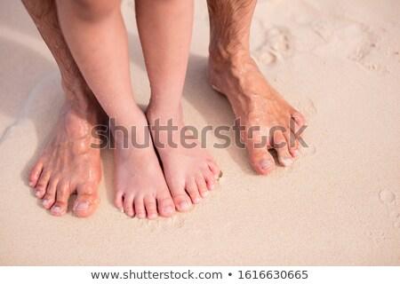 Tropical beach, legs in sand. Stock photo © dariazu