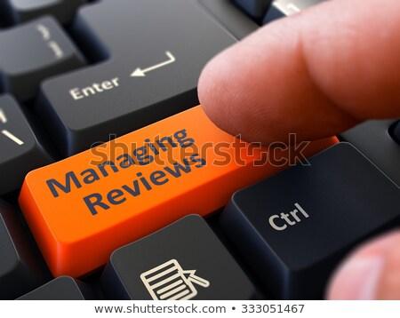 pressing orange button managing reviews on black keyboard stock photo © tashatuvango