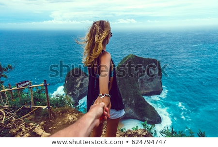 Woman wanting her man to follow her in vacation or honeymoon to beach by the ocean Stock photo © Kzenon