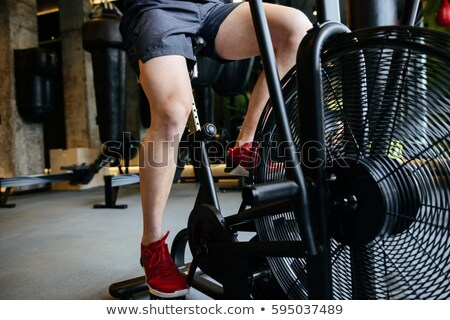 Cropped image of Athletic man using spinning bicycle Stock photo © deandrobot