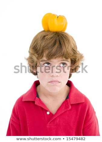 Young boy with yellow pepper on his head frowning stock photo © monkey_business