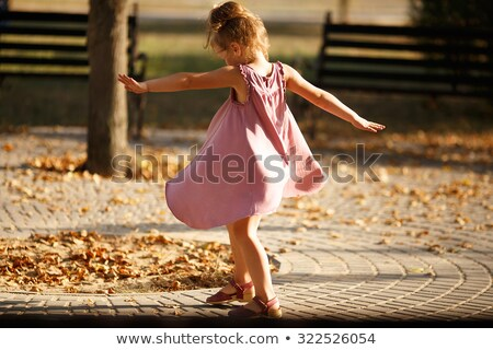 full length portrait of a happy young girl spinning around stock photo © deandrobot