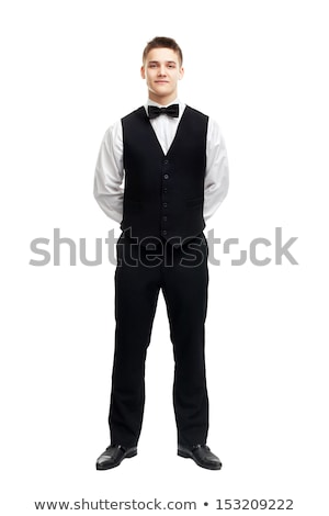 portrait of a smiling young waiter in tuxedo stock photo © deandrobot