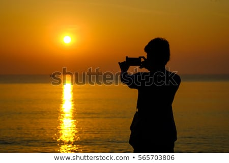 A man takes a selfie on the background of the sea and sunset VERTICAL FORMAT for Instagram mobile st Stock photo © galitskaya