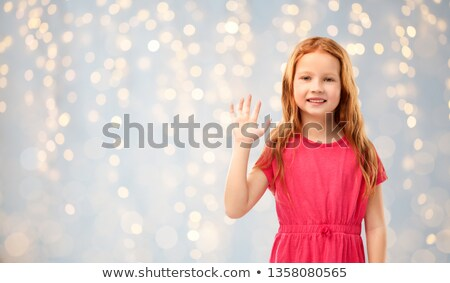 smiling red haired girl waving hand over lights Stock photo © dolgachov