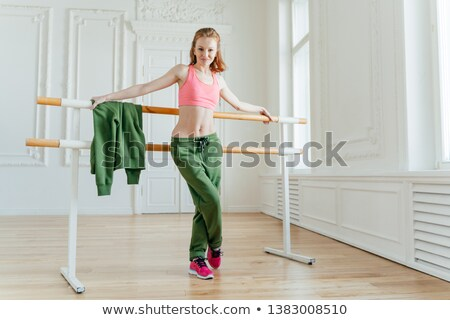 Full length shot of fit female model with bare stomach, leans at ballet barre, warms up in dancing s Stock photo © vkstudio