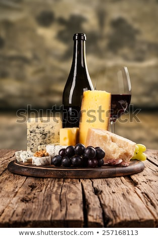 Selection of various cheese on the board and grapes on wooden background. Blue Stilton, Red Leiceste Stock photo © DenisMArt