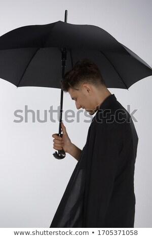 Young man with large black umbrella Stock photo © pzaxe
