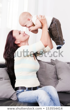 Beautiful mother playing his beby the home. Stock photo © justinb