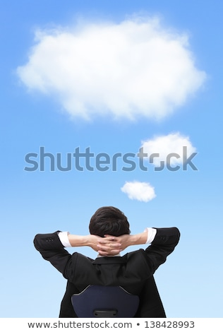 Businessman and a cloud of thoughts on a blue background Stock photo © hasloo