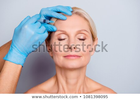 Stock photo: Needle injection on mature woman face