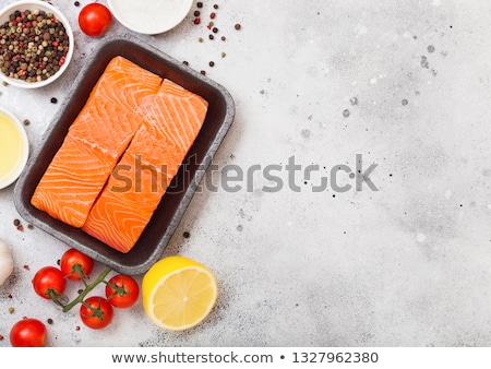 Plastic container with fresh salmon slice with oil tomatoes and lemon on wooden kitchen background.  stock photo © DenisMArt