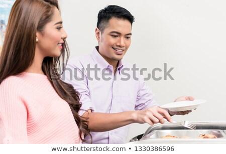 Femme regarder homme buffet alimentaire Photo stock © Kzenon