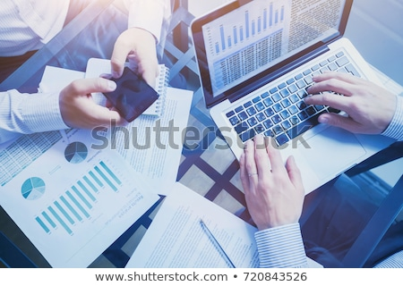 hand working in phone graphs and charts and reports concept around stock photo © ra2studio