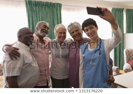 front view of senior people and female doctor taking selfie with mobile phone in living room at home stock photo © wavebreak_media