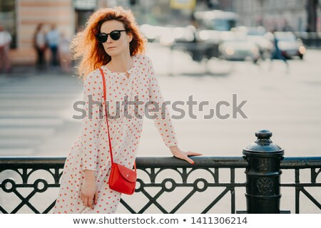 Shot of thoughtful red haired curly woman focused aside, wears long white dress, poses near black he Stock photo © vkstudio