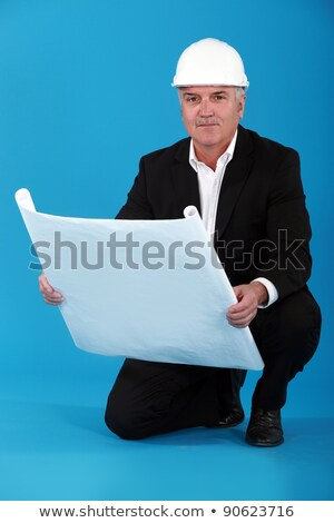 Grey-haired architect stood with plans Stock photo © photography33