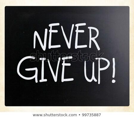 never give uphandwritten by white chalk on a blackboard stock photo © tashatuvango
