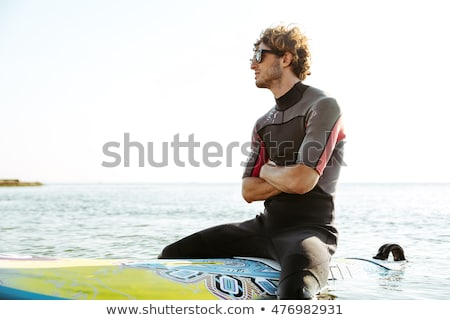 Surfer sitting on his surf board in water wearing swimsuit Stock photo © deandrobot