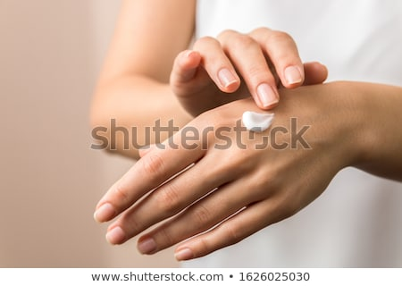 Closeup shot of woman applying moisturizing cream on hands, isol Stock photo © Nobilior