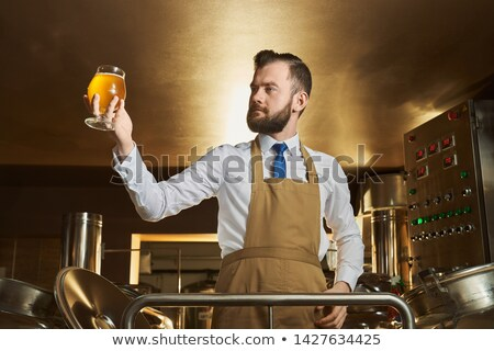 Man holding beer glass by machinery Stock photo © wavebreak_media