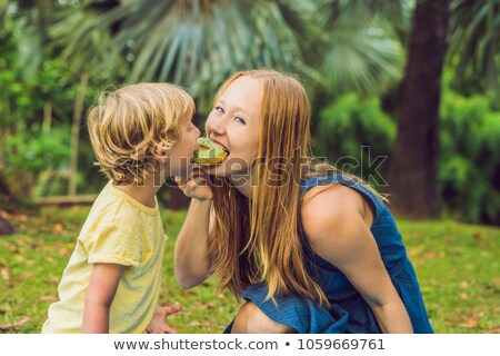 Mother and son are eating a donut in the park. Harmful nutrition in the family Stock photo © galitskaya