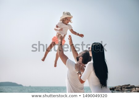 Father Throwing Her Daughter Up At Beach Stock photo © AndreyPopov