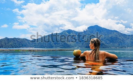 Woman on poolside with coconut relaxing in the holidays Stock photo © Kzenon