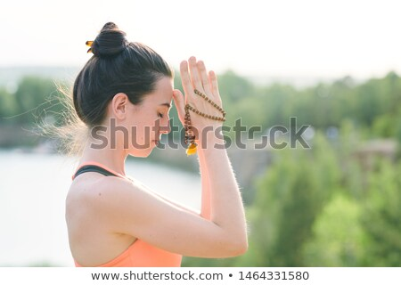 Concentrated young woman with hair bun holding mala beads Stock photo © pressmaster
