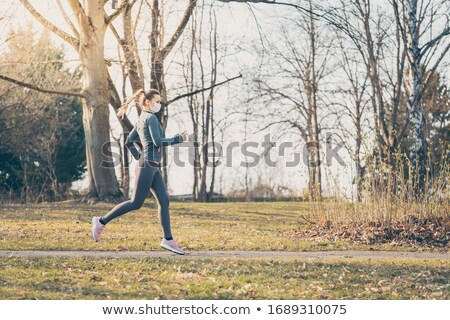 Woman wants to retain her fitness during covid-19 crises by running Stock photo © Kzenon