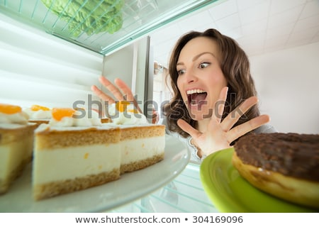 Happy Young Woman Looking At Donut From Refrigerator Stock photo © AndreyPopov