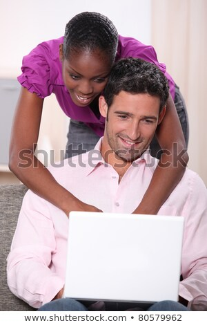 black woman leaning on his boyfriend  and doing computer laid on his boyfriend's knees Stock photo © photography33