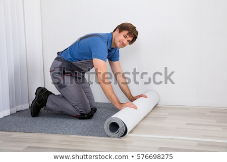 Man unrolling carpet Stock photo © photography33
