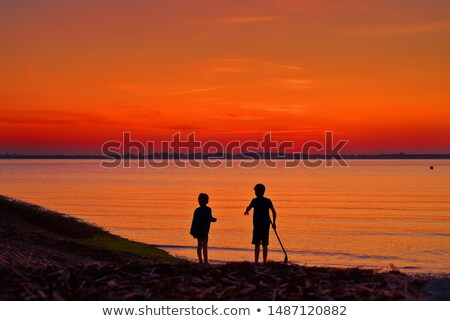 Menino olhando mar pôr do sol em pé Foto stock © vkraskouski