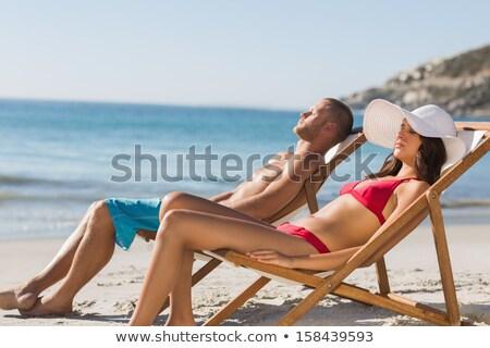 Stockfoto: Loving Couple Sunbathe On The Sun Loungers On The Beach