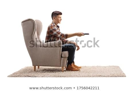 человека пультом контроль сидят гостиной Сток-фото © boggy