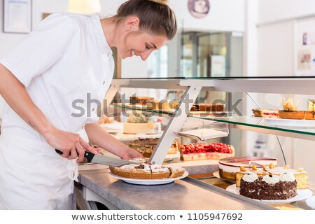 baker sales woman putting pies and cakes on display stock photo © kzenon
