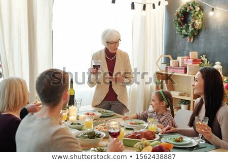 Senior grey-haired woman with glass of red wine pronouncing Thanksgiving toast Stock photo © pressmaster