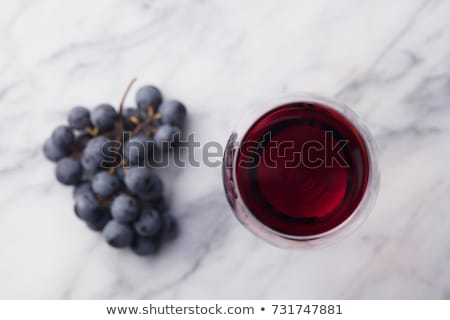 Glass of red wine on marble board on black background. Space for text Stock photo © DenisMArt