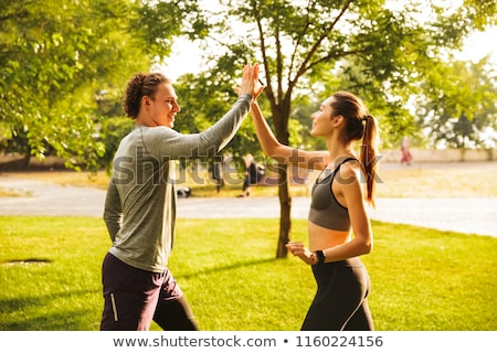 Image of attractive sportsman in tracksuit doing workout on yoga Stock photo © deandrobot