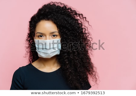 Serious dark skinned young woman being on self isolation at home, wears protective medical mask, bei Stock photo © vkstudio