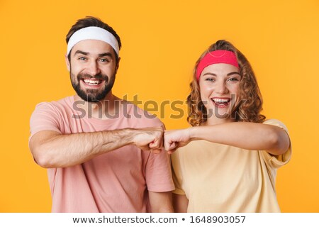 Portrait of athletic couple smiling and bumping their fists toge Stock photo © deandrobot